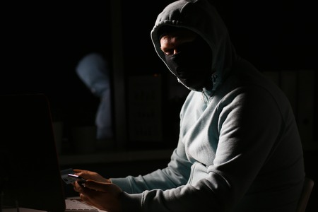 Man carder in mask connect to darknet Stock Photo
