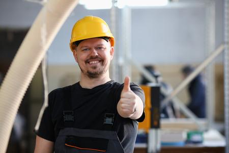 Lächelnder Arbeiter mit gelbem Helm zeigt Zeichen Standard-Bild