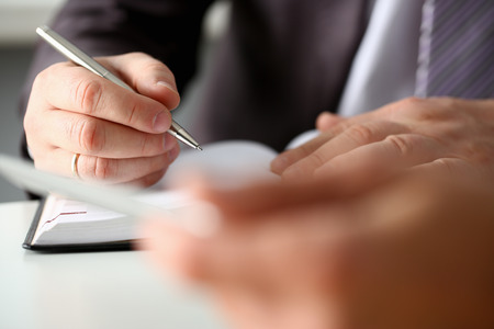 Hand of businessman in suit filling Stock Photo
