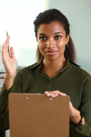 A businesswoman holds a hand up with a pen