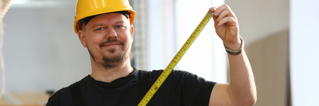 Arms of worker measuring wooden bar closeup Stockfoto