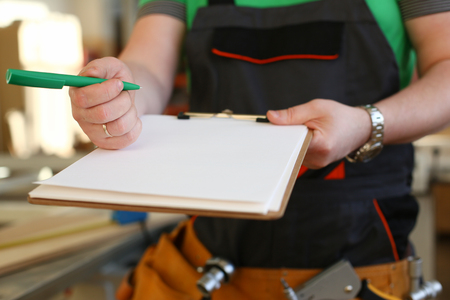 Arms of worker offer clipboard with green pen