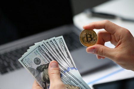 Male hand holds bitcoin and dollar coin on