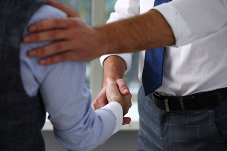 Man in suit and tie give hand as hello in office closeup Stock Photo