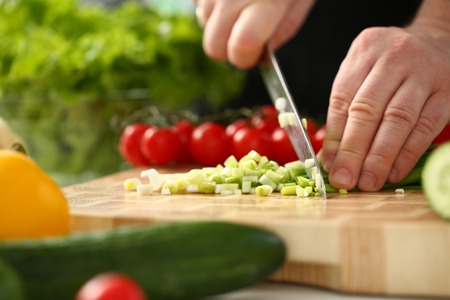 Cook holds knife in hand and cuts on Stockfoto