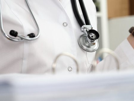 Stethoscope lying on female therapeutist doctor chest