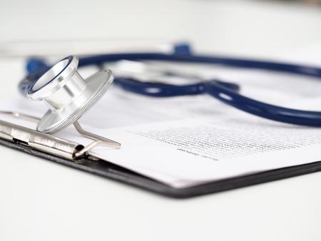 Stethoscope head lying on medical form on clipboard pad Stockfoto