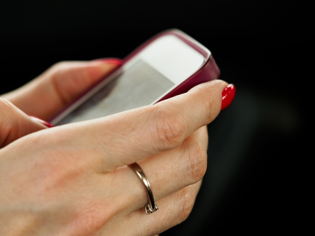 Businesswoman arm hold and use cellphone closeup