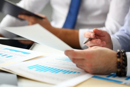 Grupo de empresarios con gráfico financiero y bolígrafo plateado Foto de archivo