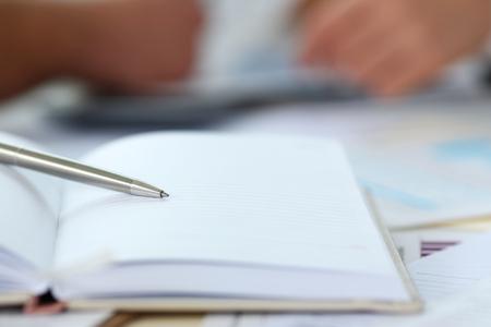Silver pen lying on opened notebook sheet