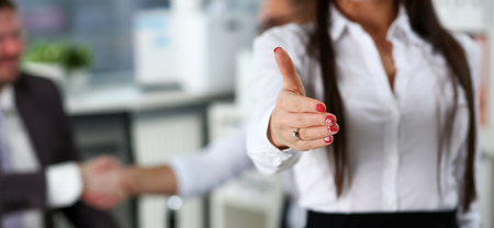 Woman in suit give hand as hello in office