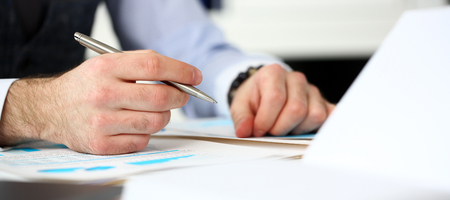 Clerk man at office workplace with silver pen in arms