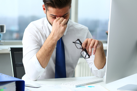 Tired clerk at laptop pc workplace wearing glasses Reklamní fotografie