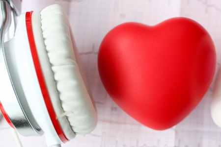 Red toy heart an heaphones on paper cardiogram