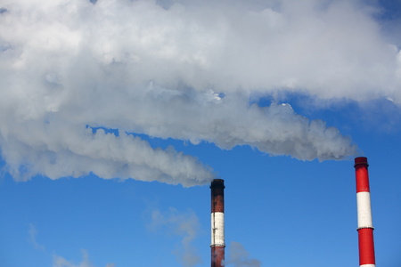 White smoke comes from pipes against blue sky Stockfoto