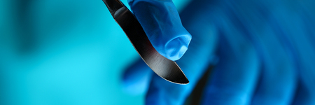 Surgeon arms in sterile uniform holding sharp knife while operating patient in surgical theatre closeup. Stop bleeding put stitch innovation er 911 team cancer tumour concept Stock fotó
