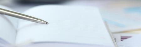 Silver pen lying on opened notebook sheet Standard-Bild - 117369757