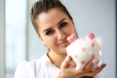 Happy beautiful woman hold in arms funny piggybank