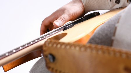 Male arms playing classic shape electric guitar
