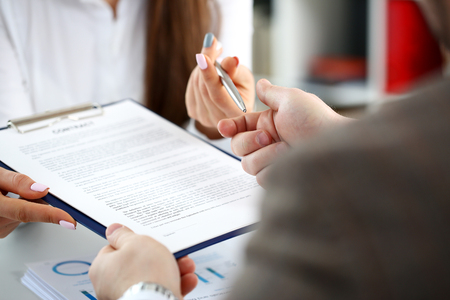 Female arm offer contract form on clipboard pad Stock Photo