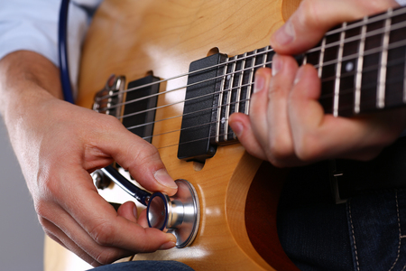 Male arms hold stethoscope head diagnosing guitar