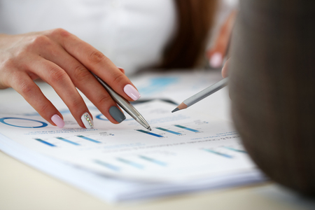 Female arm holding silver pen point in financial graph