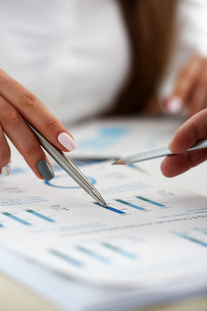 Female arm holding silver pen point in financial graph solving and discussing problem with colleague closeup. Situation examination at board council sale adviser job stock exchange market profit Stock Photo