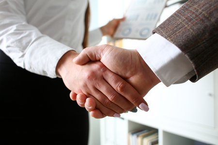 Man in suit and tie give hand as hello in office Stock Photo
