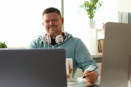 Handsome smiling male student using online education service and drink tea or coffee. Young man looking in laptop display watching training course and listening it with headphones.