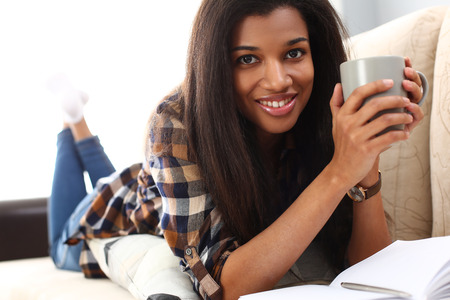 Smiling black woman lie down at sofa with cup of hot beverage