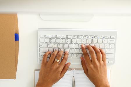 Hand van zwarte vrouw typt iets met wit draadloos computertoetsenbord Stockfoto