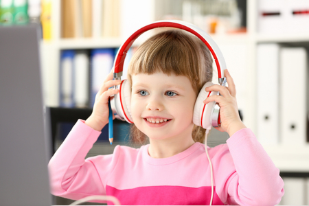 Little girl wearing headphones use mobile computer