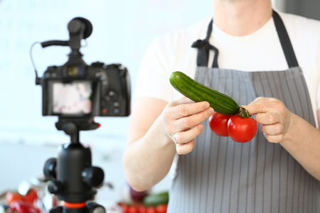 Male hand blogger hold cucumber and tomatoes