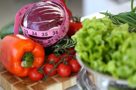 Ruban à mesurer allongé sur une table avec des produits frais