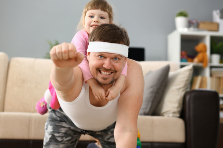 Cute little girl riding her father at home playing