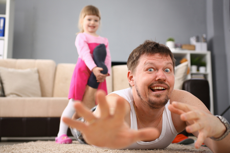 Cute little girl hold her father leg as proof of winning battle game