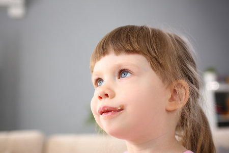 Little girl eating sweet chocolate candy with trace at her mouth