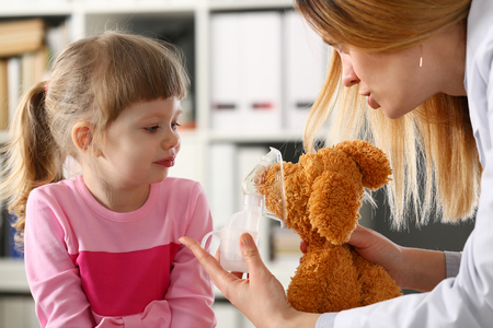 Doctor play with little patient giving inhaler to toy