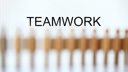 Teamwork sign above line of toy human figures