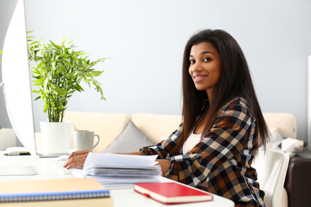 Black smiling woman sitting at workplace working with desktop pc