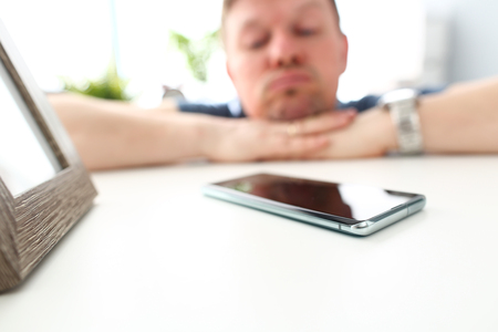 Cellphone lying on table with pensive man in background waiting for call