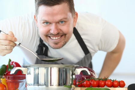 Satisfied Culinary Chef Holding Kitchen Spoon