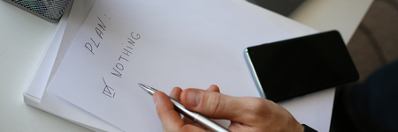Male hand hold silver pen composing to do list Standard-Bild