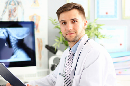 Smiling male doctor working with compute in his office