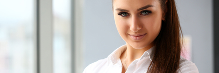 Beautiful smiling girl at workplace look in camera Фото со стока
