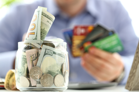 Big jar full of money stand at working table with male hand holding bunch of credit cards Stockfoto