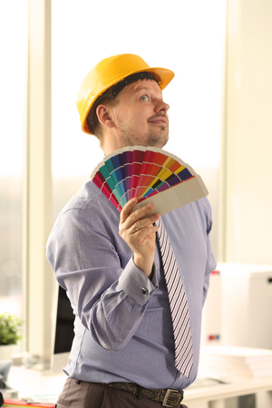 Male Caucasian Decorator Holding Colour Swatches