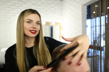 Young Woman Hairdresser Making Haircut with Comb Imagens
