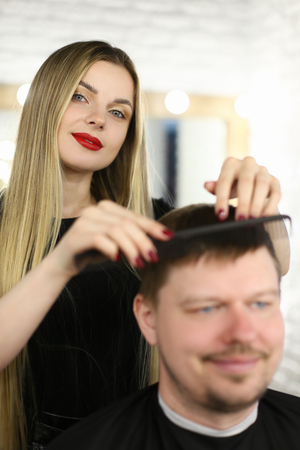 Woman Hairstylist Combing Client with Hairbrush Imagens