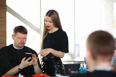 Man Client Showing on Phone to Woman Hairdresser Imagens
